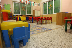 Interiors of a nursery class with colored drawings of children. Interiors of a nursery class with coloredchairs and drawings of children hanging on the walls stock images