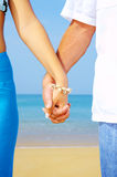 Interlacing. View of a young couple holding hands on the beach stock image