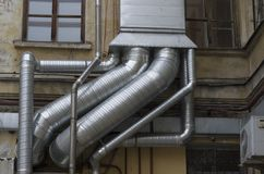 Interlacing of silver air ducts. Of different diameters on the old building royalty free stock photo