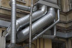 Interlacing of silver air ducts of different diameters. On the old building closeup royalty free stock image