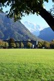 Interlaken, la Svizzera, A tre, giardino del prato inglese, costruzione e montagne fotografie stock