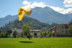 Interlaken/Schweiz - Juli 17 2018: Paragliderlandning på en grön gräsmatta arkivfoton