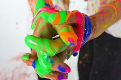 Interlocked Fingers with Colorful Paint. Two kids holding hands with colorful finger paint mixing together in a big mess Stock Photography
