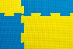 Interlocking blue and yellow EVA foam flooring tiles inside a gym, nursery, play room or school. Interlocking blue and yellow EVA foam flooring tiles inside a royalty free stock images