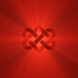 Interlocking heart knot shine light flare. Interlocking red heart knot symbol illustrated with powerful light flares. Metaphor for forever love, wedding Royalty Free Stock Photo