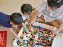 Interlocking plastic bricks in mother`s hands being built with help from her two little babies. Toys can be used as a tool to build up mother-and-baby royalty free stock photos