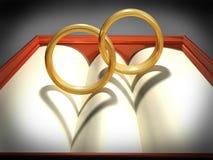 Interlocking wedding rings. Two interlocking wedding rings with heart shadows Stock Photo