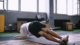 Intermediate no equipmetn exersize to endurance, sit ups. High performance triathlon or marathon exercises. Man in good fit does left side plank wraps for stock video