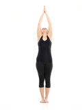 Intermediate yoga pose. Preparation for yoga posture, demonstrated by young woman, dressed in black, on white background Stock Photo