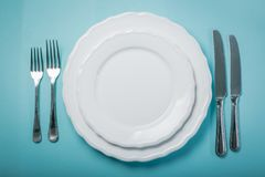 Intermittent fastin concept - empty plate on blue background. Copy space Stock Photo