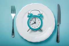 Intermittent fastin concept - empty plate on blue background. Copy space Royalty Free Stock Photo