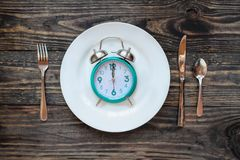 Intermittent Fasting Concept with Clock on Plate. Twelve hour intermittent fasting time concept with clock on plate over a rustic wooden table / background. Top stock photos