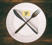 Intermittent Fasting Cross with Knife Fork and Note on Plate Stock Photography