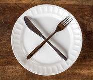 Intermittent Fasting Cross with Knife and Fork on Plate Royalty Free Stock Image