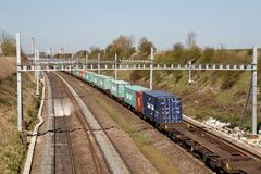 Intermodal freight train. MORETON, UK - APRIL 20: An intermodal diesel freight train heads towards Bristol on April 20, 2016 in Moreton. This service is passing Stock Photo