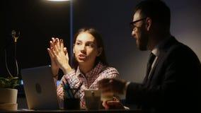 Intern die aan mentor luisteren die instructies geven die bij laat bureau zitten stock videobeelden
