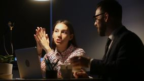 Intern listening to mentor giving instructions sitting at desk late