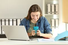 Intern reading message in a smart phone at office. Front view portrait of a distracted intern reading messages in a smart phone at office Stock Photos