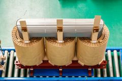 Internal active parts core and coils of transformer. Internal active parts core and coils of three phase distribution oil immersed transformer during in Royalty Free Stock Photo