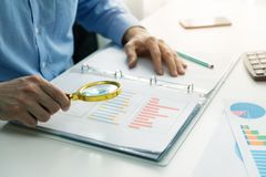 Internal audit concept. Man with magnifying glass inspecting business documents Stock Photos