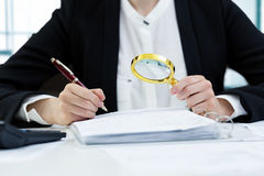 Internal audit concept - woman with magnifying glass inspecting. Documents in office stock image