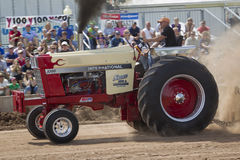 International 1066 tractor and smoke. DE PERE, WI - AUGUST 18: A red & white International 1066 tractor competing at the Tractor Pull event at the Brown County royalty free stock images