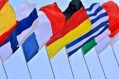 International activity with countries flags. Different countries national flags getting together under blue sky, shown as worldwide, country, and international Stock Image