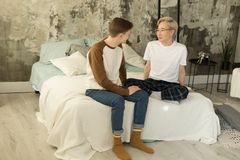 International adult relationships. Two gay male partners in casual clothes resting together in one bed stock photography
