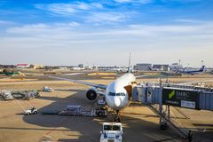 International airplane waiting for passengers to board and loading cargo royalty free stock photos