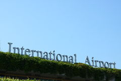 International Airport Sign. With hedge in the foreground Royalty Free Stock Photography