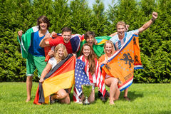 International Athletes With Various National Flags Celebrating I. Portrait of cheerful young multiethnic athletes with various national flags celebrating in park Stock Photo