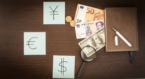 International Banknotes, coins, notepad, stickers with currency signs on wooden table. Royalty Free Stock Photos