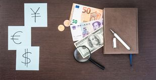 International Banknotes, coins, notepad, stickers with currency signs on wooden table. Copy space. Stock Photos