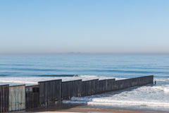 International Border Wall Extending to Pacific Ocean. The international border wall extending out into the ocean and separating San Diego, California from Royalty Free Stock Images