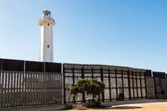 International Border Wall at Friendship Park and El Faro Lighthouse in Tijuana. SAN DIEGO, CALIFORNIA - NOVEMBER 4, 2017: People communicate through the royalty free stock photo