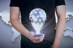 International business and communications concept. Young guy holding smartphone with creative terrestrial globe on grey background with abstract map Royalty Free Stock Image