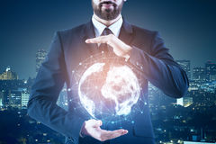 International business concept. Businessman holding abstract glowing globe on blurry night city background. International business  concept Stock Images