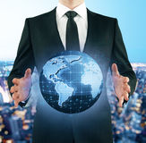 International business concept. Businessman in suit holding abstract digital terrestrial globe on city background. International business concept. 3D Rendering Stock Photography