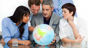 International business people looking at a globe Stock Photo