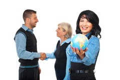 International business relationship. Happy business woman holding a world globe while two other business people shaking hands in background concept of Royalty Free Stock Images