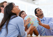 International business team holding a globe. International business team holding a terrestrial globe looking at the top in their modern building Stock Photos
