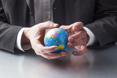 International businessman holding the globe in his hands Stock Photography