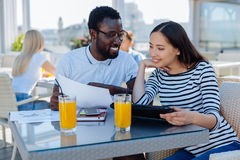 International chatting over homework in cafe. What do you think about it. Handsome african american guy showing his female groupmate a printout and asking her Royalty Free Stock Photo