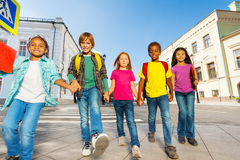 International children wear bags and walk in row Stock Photo