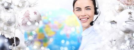 International christmas smiling woman with globe and headset on. Christmas balls background Royalty Free Stock Photography