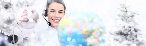 International christmas smiling woman with globe and headset on. Christmas balls background Royalty Free Stock Images