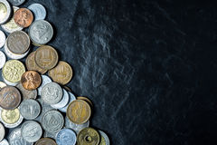 International coins background on black stone table top texture, Royalty Free Stock Photography