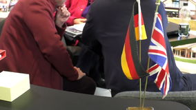 International collaboration.German British flags. Small German and British flags on the desk in focus, people in the background sitting at the table and talking stock footage