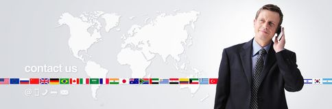 International contact us concept, businessman with mobile phone isolated on world map background, flags icons and contact symbols stock image