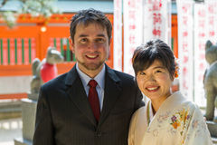 International Couple at Japanese Shrine. An international couple, White and Japanese, pose in suit and kimono in front of a shrine royalty free stock photos